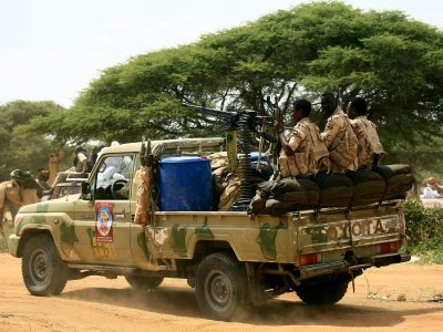 Sudanese members of the Rapid Support Forces, a paramilitary force backed by the Sudanese government to fight rebels and guard the Sudan-Libya border, ride in the back of a Toyota pickup truck as they prepare to receive President Omar al-Bashir during his visit to the town of Umm al-Qura, northwest of Nyala in South Darfur province, on September 23, 2017. Bashir, wanted by the International Criminal Court on charges of genocide and war crimes related to the conflict in Darfur, is touring the region ahead of a US decision to be made on October 12, 2017 on whether to permanently lift a decades-old trade embargo on Sudan. / AFP PHOTO / ASHRAF SHAZLY        (Photo credit should read ASHRAF SHAZLY/AFP/Getty Images)